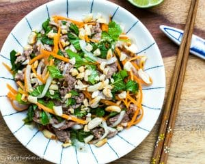 Vietnamese Rare Beef in lime juice salad (bo tai chanh) consists of beef cured in lime juice, crunchy veggies, refreshing herbs and roasted peanuts.