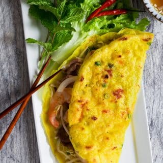 Vietnamese Crepe (Banh Xeo) is thin, crispy and filled with shrimp, pork, and crunchy vegetables. This delicious crepe is quick and easy to make. Serve it with fresh herbs and refreshing lime fish dipping sauce as a snack, appetizer or main dish.