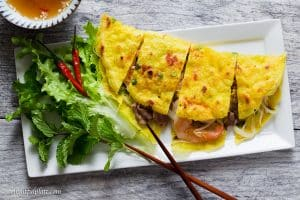 Vietnamese Crepe (Banh Xeo) is crispy, light and filled with shrimp, pork, and crunchy vegetables. Serve it with fresh herbs and refreshing dipping sauce as a snack, appetizer or main dish.
