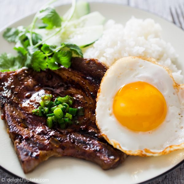 Vietnamese grilled lemongrass pork chops served with a fried egg and rice.