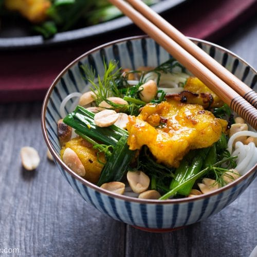 A bowl of vermicelli noodles, topped with Vietnamese turmeric fish, scallion, dish and roasted peanut. Cha Ca La Vong is an iconic dish of Hanoi.