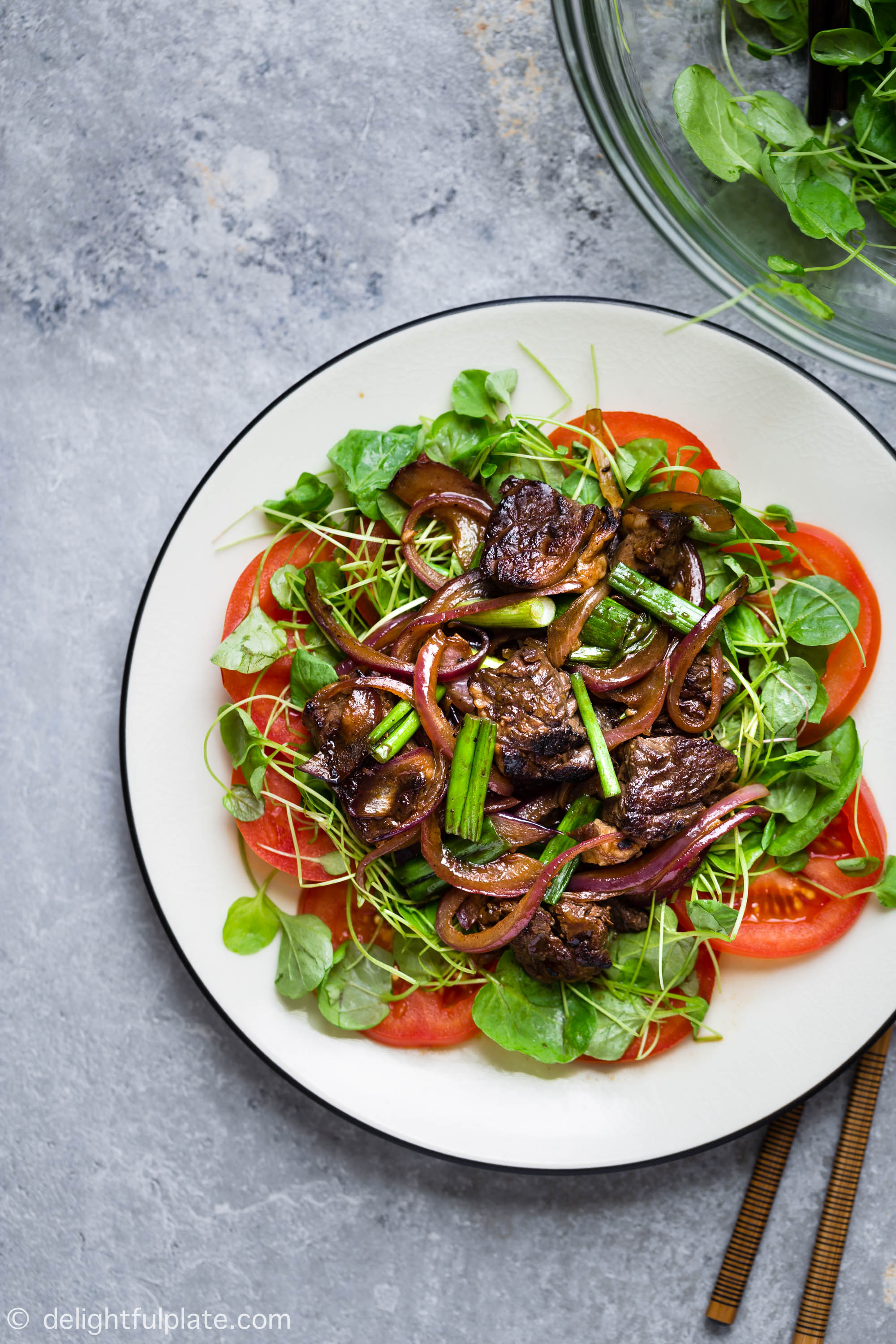 Vietnamese Shaking Beef (Bo Luc Lac) is a popular Southern dish that is excellent for everyday meals as well as special occasions. This dish features tender and flavorful beef cubes plated on a bed of watercress and fresh tomatoes.