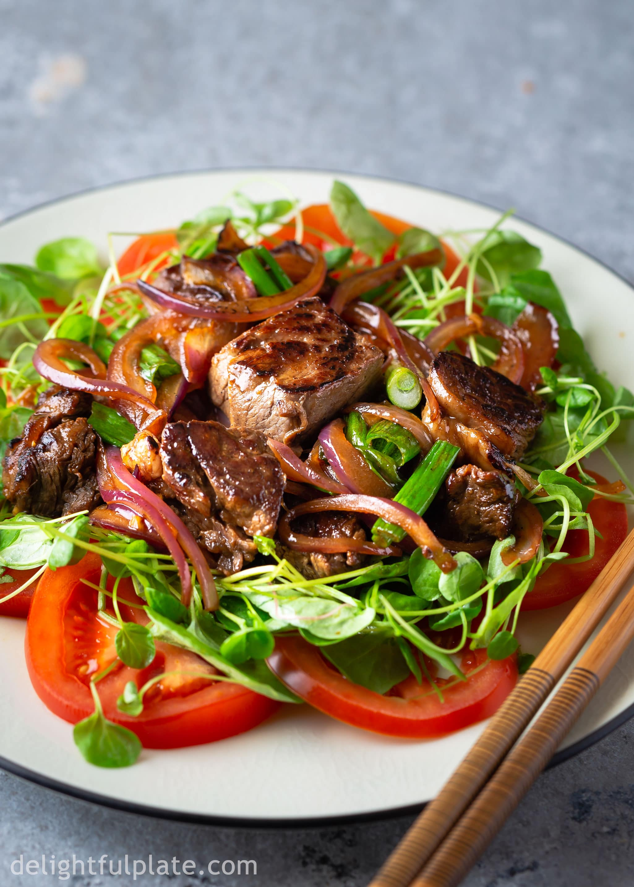 Vietnamese Shaking Beef (Bo Luc Lac) with flavorful seared beef cubes and tomato and cress salad.