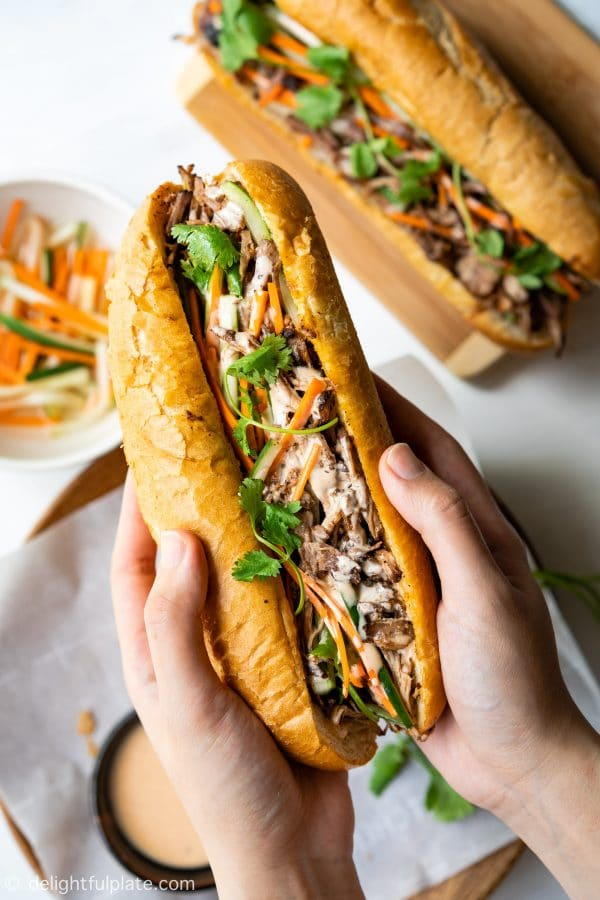 This Vietnamese Pulled Pork Banh Mi features crispy bread, tender and flavorful pork, crunchy pickled vegetables and yummy sriracha mayo sauce. With the help of a slow cooker, this banh mi sandwich recipe is super easy to make.