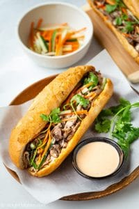 This pulled pork banh mi features Vietnamese baguette (banh mi) filled with tender and flavorful pulled pork, pickled vegetables, and tasty sriracha mayo sauce. With a slow cooker to cook the pulled pork, this delicious banh mi recipe cannot be easier to make.