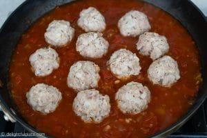 Cooking Vietnamese meatballs in tomato sauce (xiu mai)