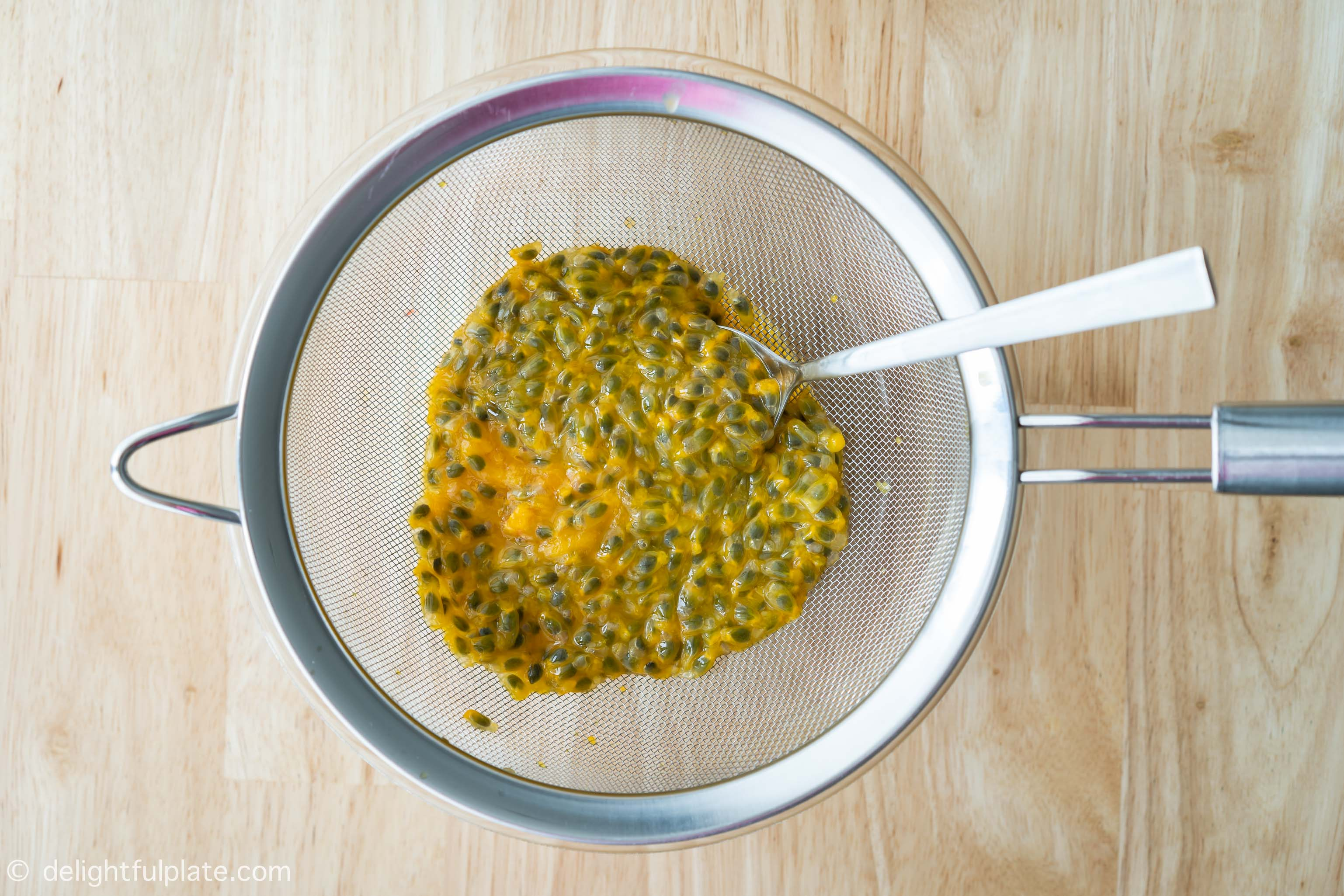 Extracting juice from passion fruits with a strainer and a spoon