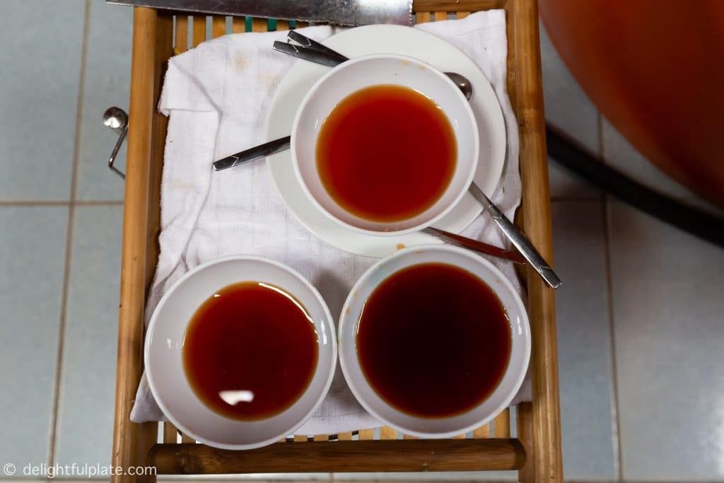 three bowls of fish sauce at different fermenting stages. The less time, the lighter the sauce.