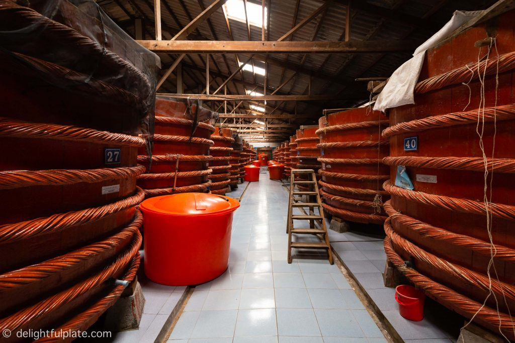 rows of huge wooden barrels inside Red Boat fish sauce factory in Phu Quoc, Vietnam