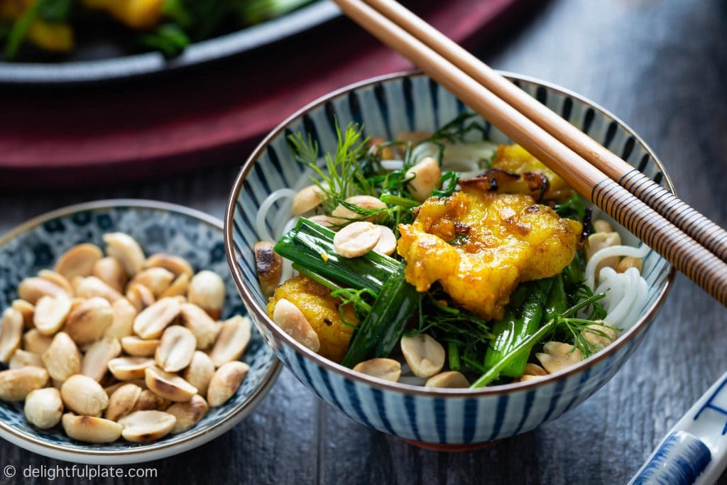 A bowl of Cha Ca Hanoi consists of melt-in-the-mouth grilled turmeric fish, cooked spring onion and dill, soft vermicelli noodles and crunchy roasted peanuts.