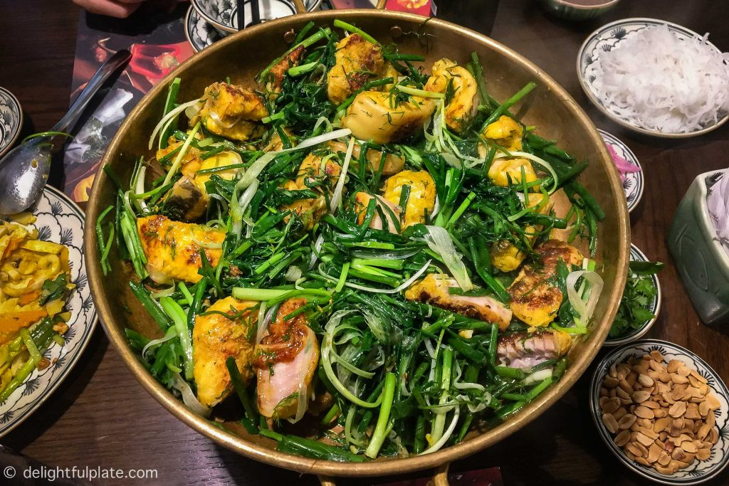 A pan of Cha Ca Hanoi with fish chunks, spring onion and dill