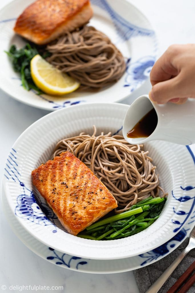 An easy and healthy salad with crispy pan-seared salmon, soba buckwheat noodles, spinach and ginger dressing.