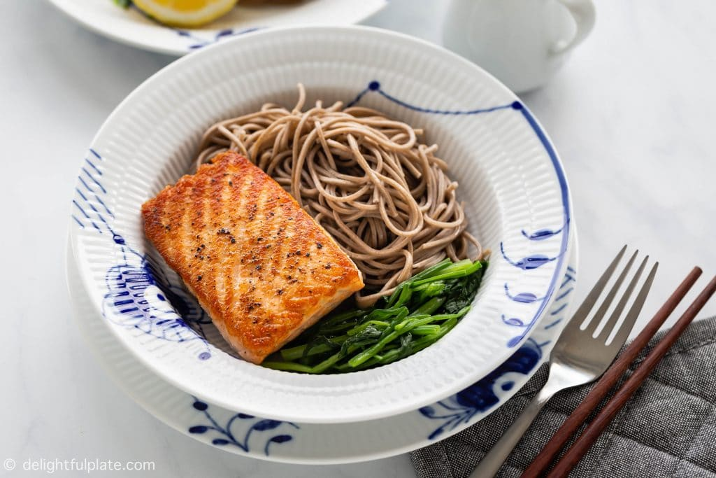 Crispy pan-seared salmon over soba buckwheat noodles and spinach. Serve with a soy-based ginger dressing.