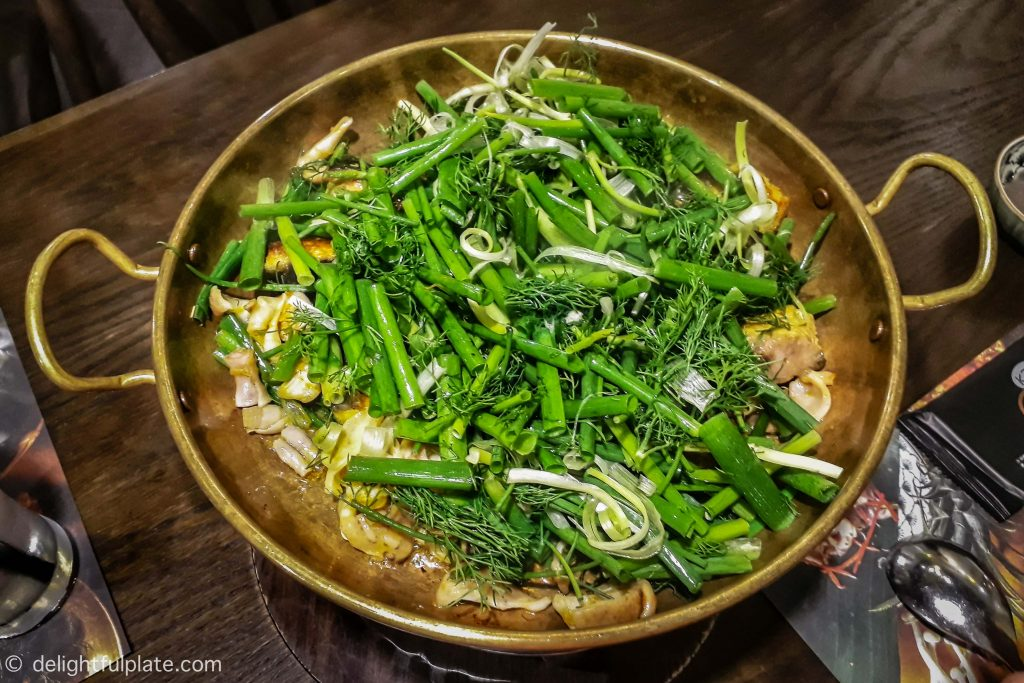 A sizzling pan of cha ca Hanoi with fried fish chunks, spring onion and dill