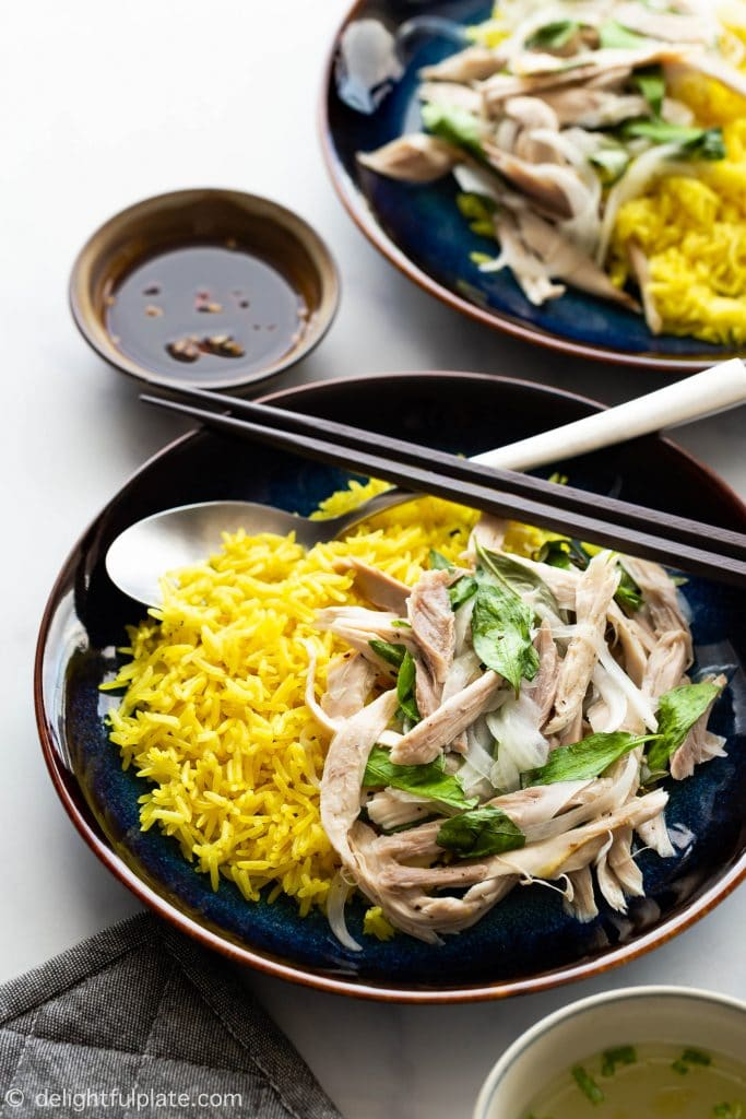 Com Ga Hoi An (Vietnamese Chicken Rice) features shredded chicken tossed with Vietnamese coriander, onions, and lime juice dressing. The chicken salad is then served with turmeric rice cooked directly in chicken stock.