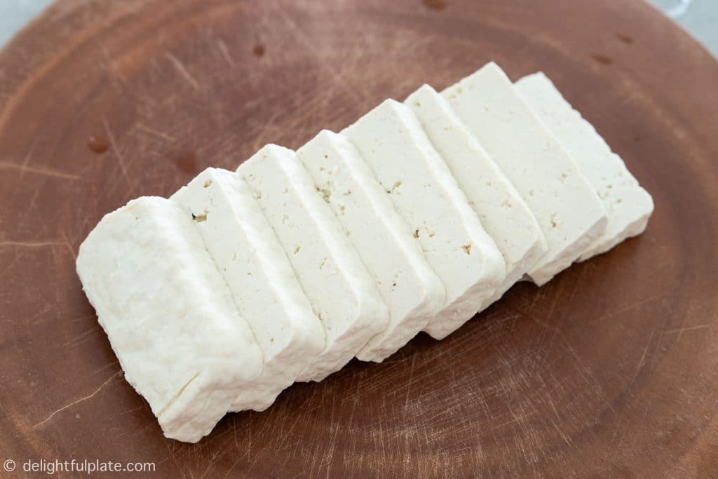 A block of tofu sliced into thin slices.
