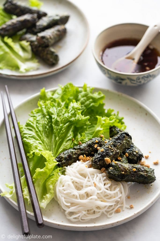 Vietnamese Grilled Beef in Wild Betel Leaves (Bo Nuong La Lot) is served with rice vermicelli noodles, lettuce, fresh herbs, roasted peanuts and sweet and sour dressing.