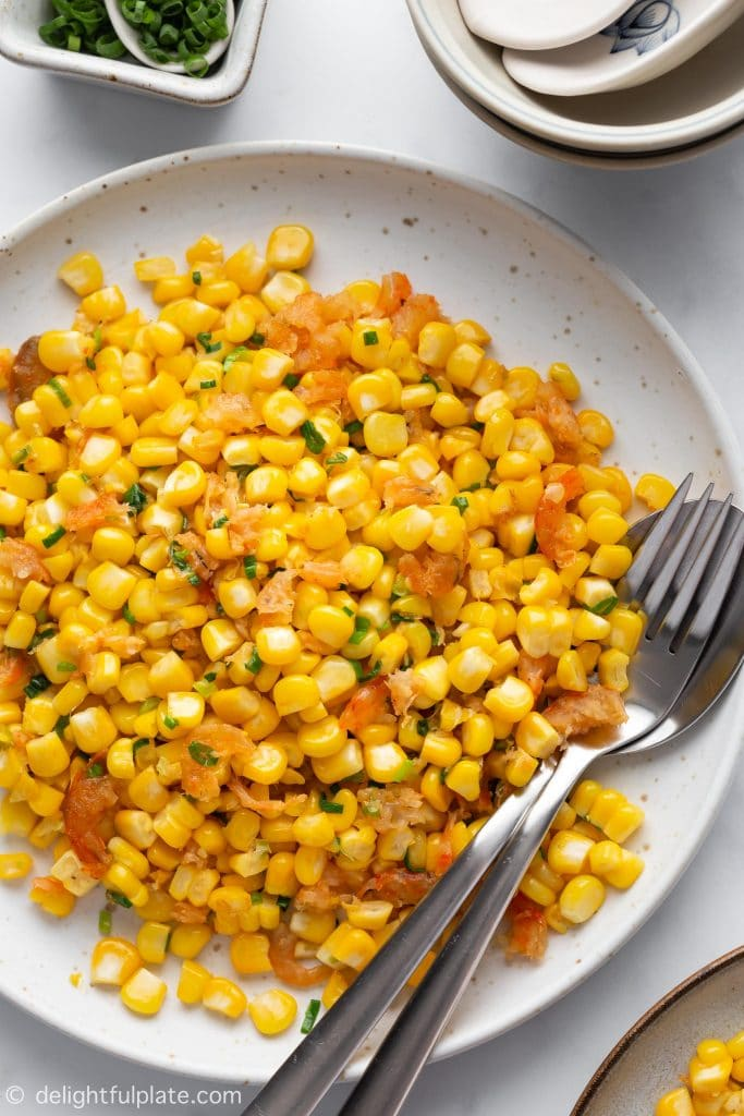 A plate of Sweet corn sautéed in butter with dried shrimps and scallions. Vietnamese Sautéed Corn with Dried Shrimps (Bap Xao) is a popular street food snack in Saigon.