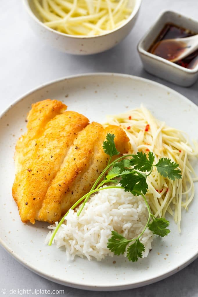 Vietnamese crispy fried fish is served with green mango salad, fish sauce dressing and steamed rice.
