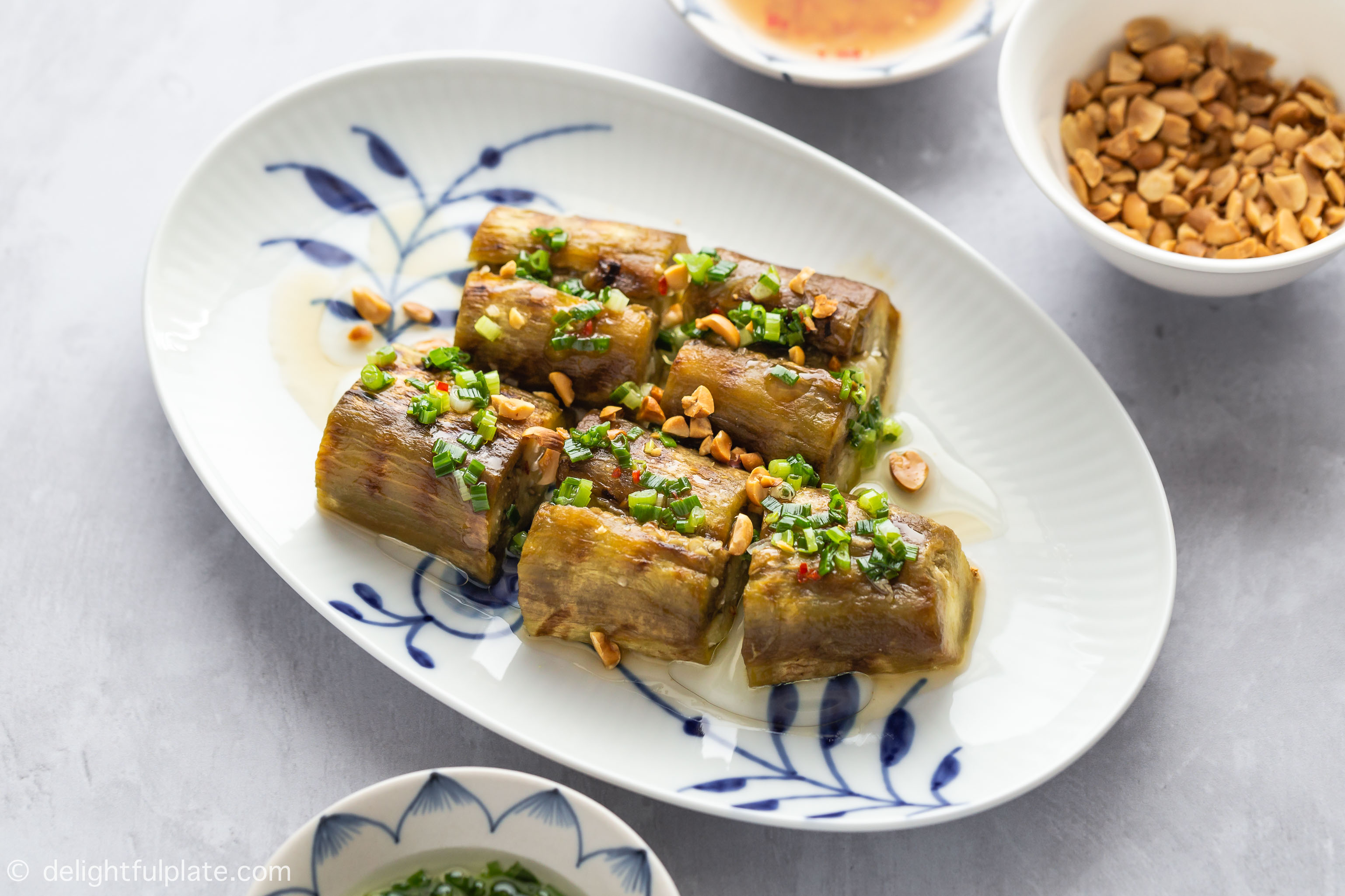 Vietnamese Whole Grilled Eggplant are topped with scallion oil, roasted peanuts and fish sauce dressing.