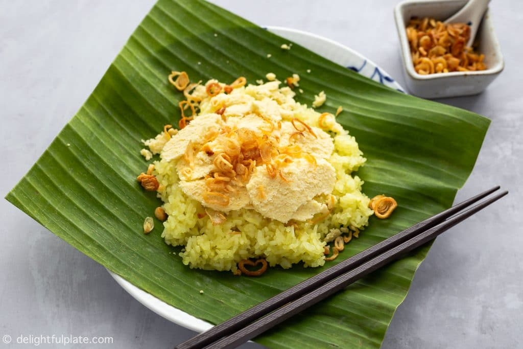 A plate of Xoi Xeo Hanoi, with Vietnamese steamed sticky rice, slices of mung bean and fried shallots.