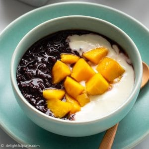 Black Sticky Rice Pudding cooked in a pressure cooker, then served with yogurt and mango