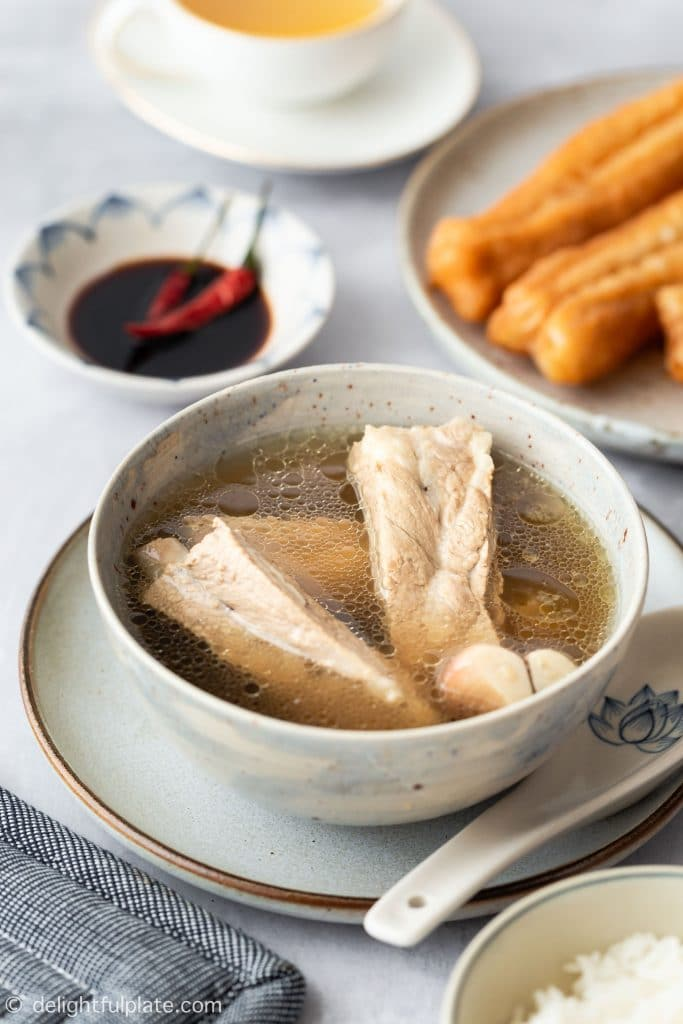 A bowl of Singapore-style bak kut teh (pork rib soup with white pepper), served with rice, youtiao, soy sauce and oolong tea.