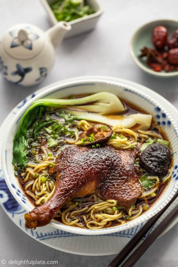 A bowl of Vietnamese Duck Noodle Soup (Mi Vit Tiem) featuring slippery noodles, fall-off-the-bone duck legs, and a dark broth.