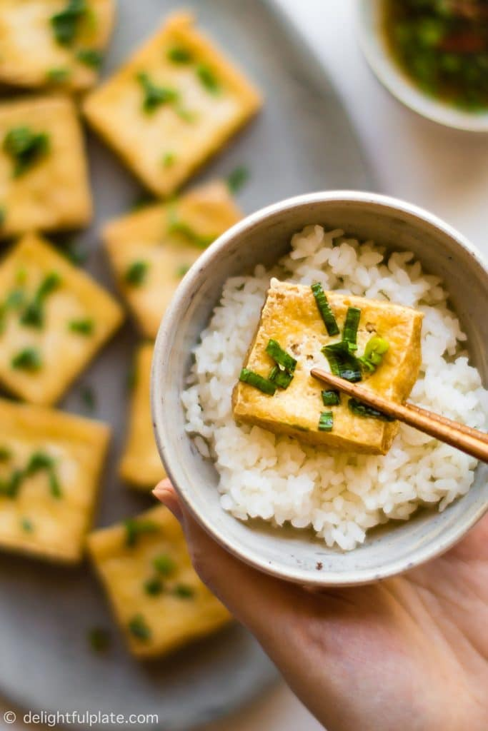 A piece of fried tofu dipped in scallion fish sauce and served with a bowl of rice.