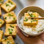 A crispy slice of tofu that has been dipped in scallion fish sauce, served with rice