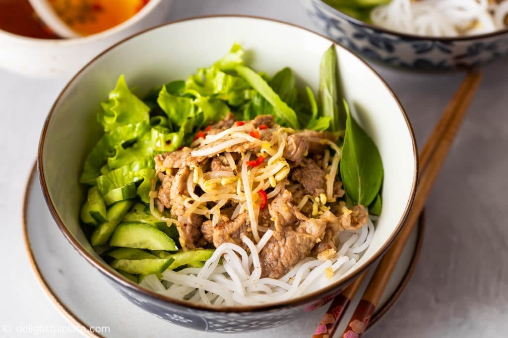 A bowl of Vietnamese lemongrass pork noodle salad (bun this xao) with stir-fried pork, beansprouts, noodles, cucumber, lettuce and herbs.