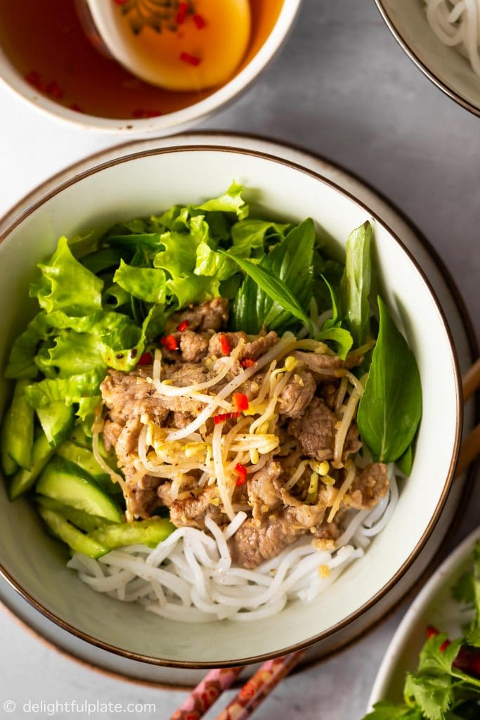 A bowl of Vietnamese lemongrass pork noodle salad (bun this xao) with stir-fried pork, beansprouts, noodles, cucumber, lettuce and herbs. Serve with dressing.
