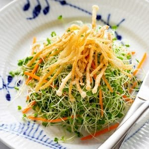 a plate of microgreens salad topped with crispy fried enoki mushrooms