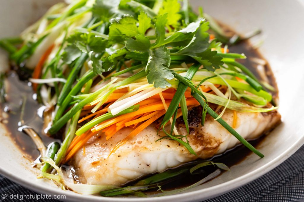 A plate of steamed fish with soy sauce, julienned ginger, scallions, onion and carrots