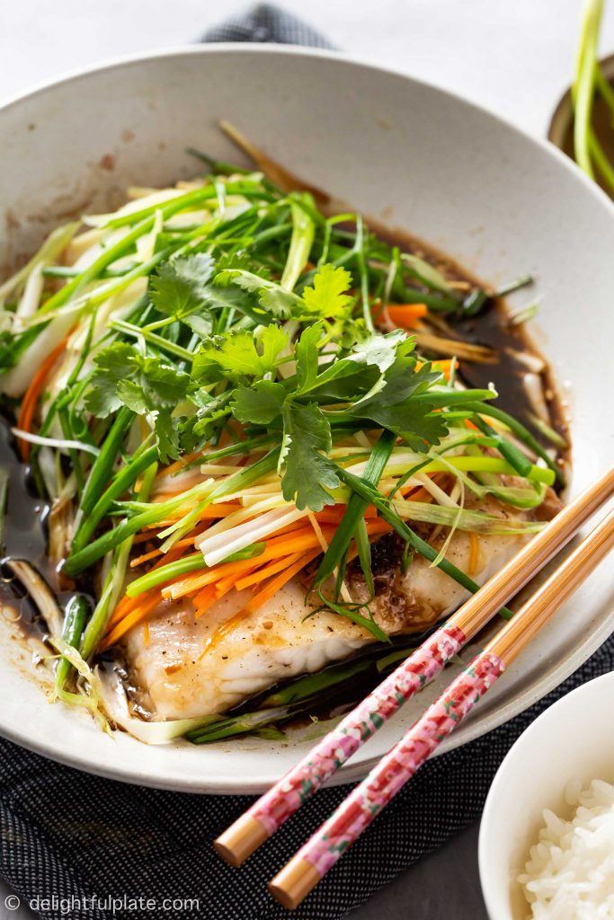 a plate of steamed fish with soy sauce, ginger, scallion, onion and carrot. Serve with rice