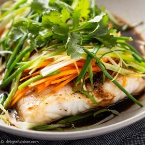 a steamed fish fillet with soy sauce, ginger, scallion, onion and carrot