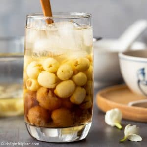 a serving glass with longan, lotus seeds soup and crushed ice