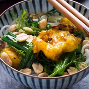 a bowl with grilled fish marinated with turmeric on top of noodles, dills and scallions