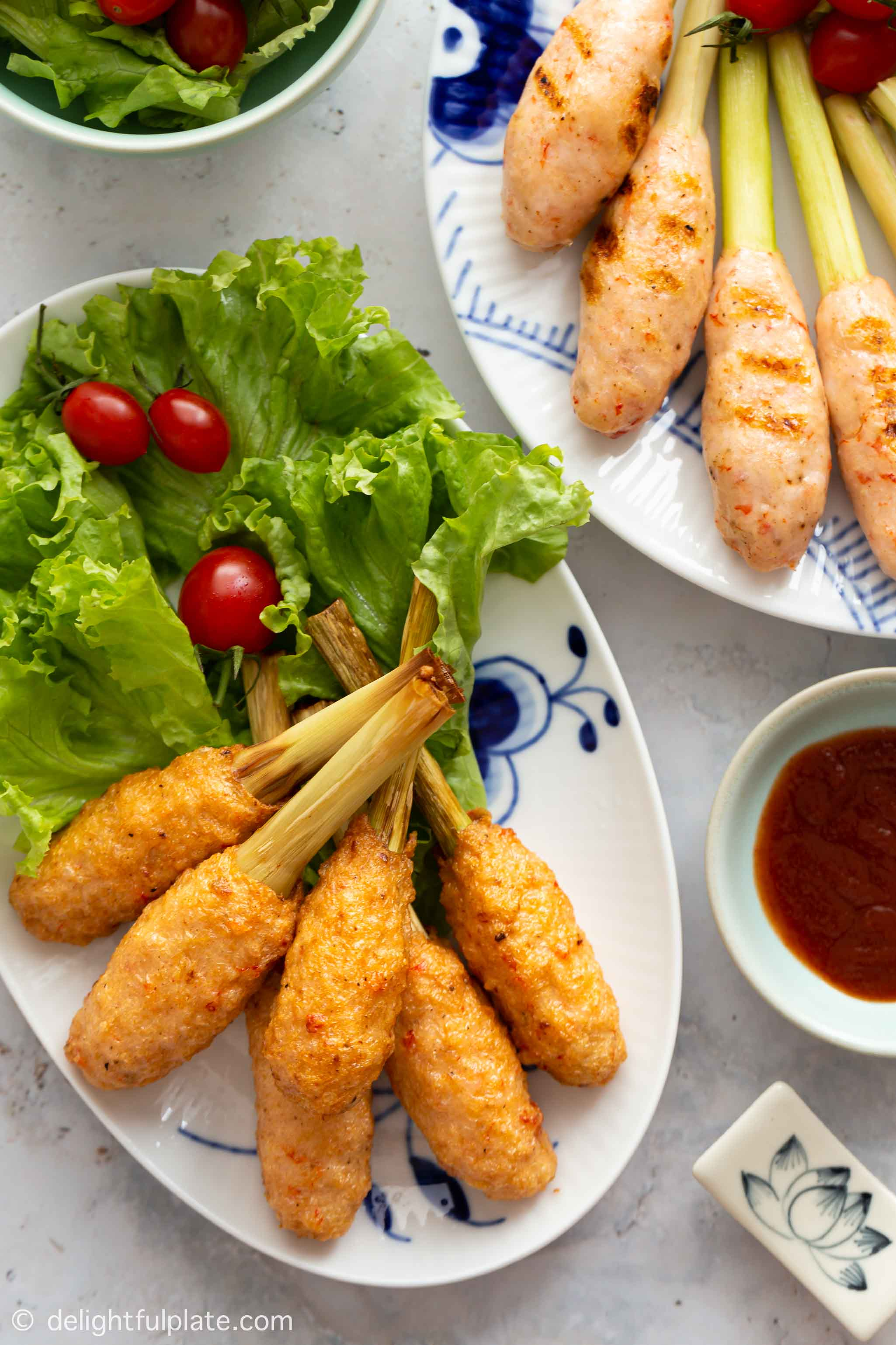 Two plates with Vietnamese shrimp on lemongrass sticks: one with fried sticks and the other one with grilled sticks