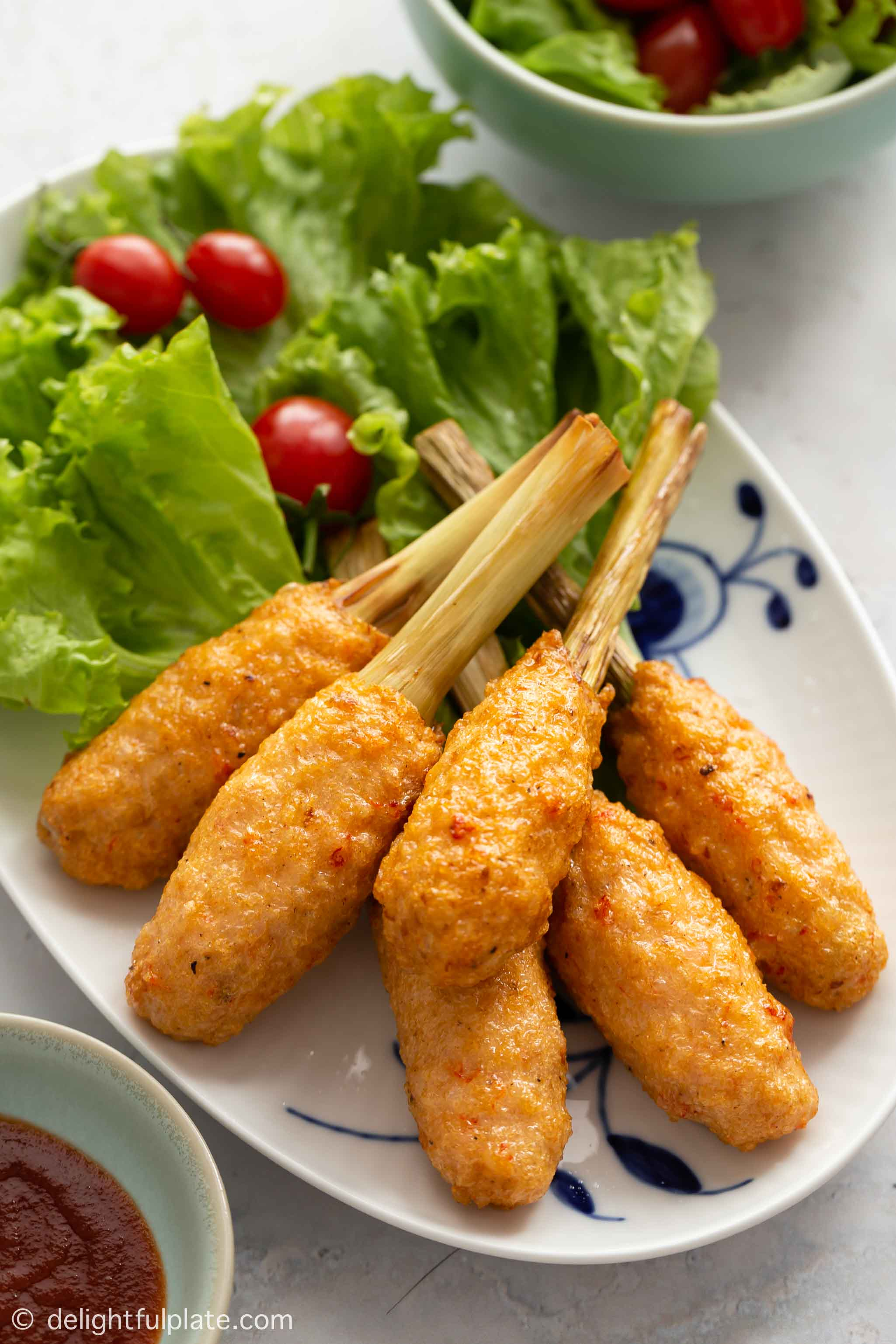 Golden Vietnamese shrimp sticks (Chao tom) on a serving plate with lettuce and cherry tomato