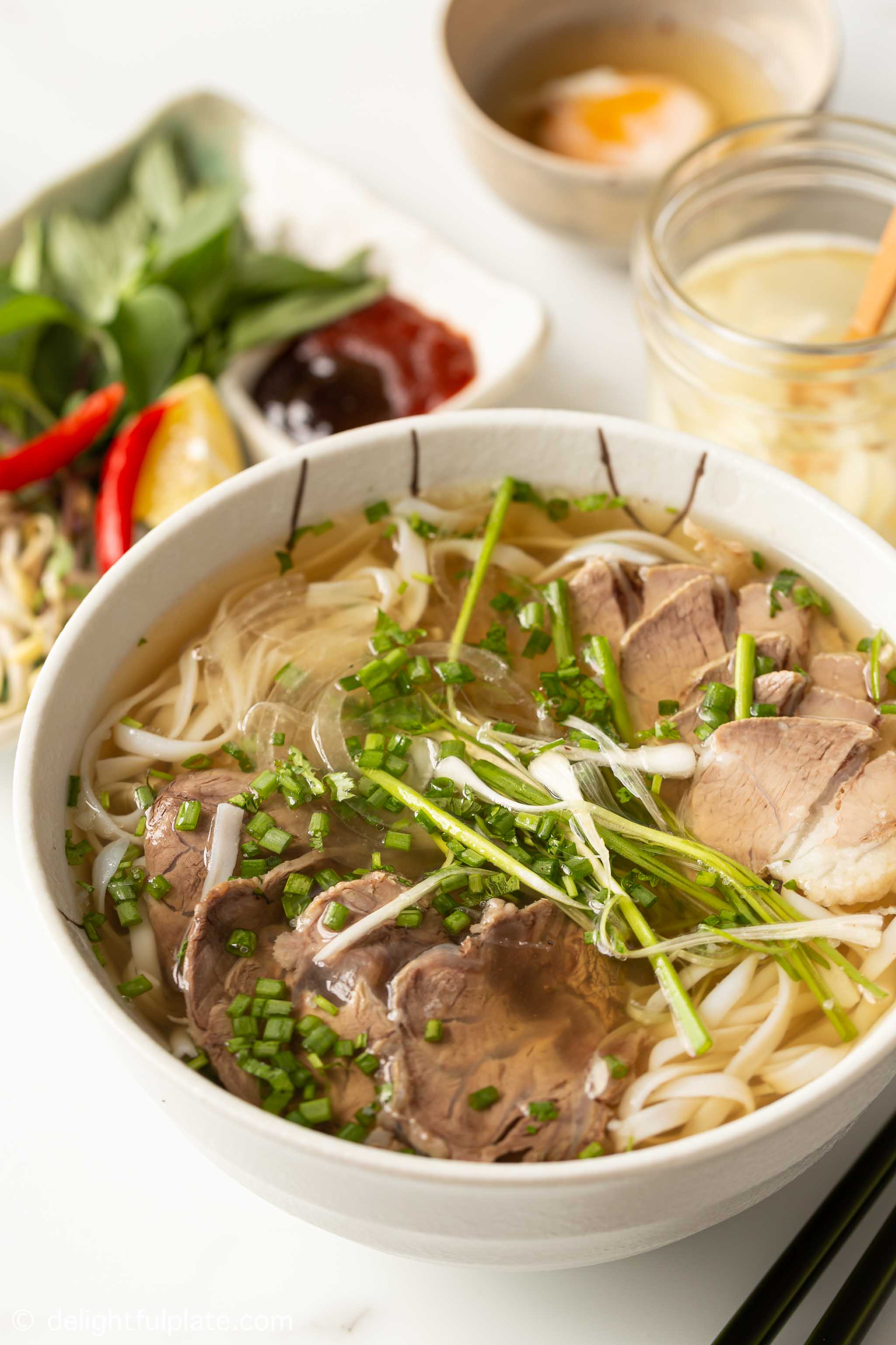 a bowl of Vietnamese beef pho noodle soup served with accompaniments
