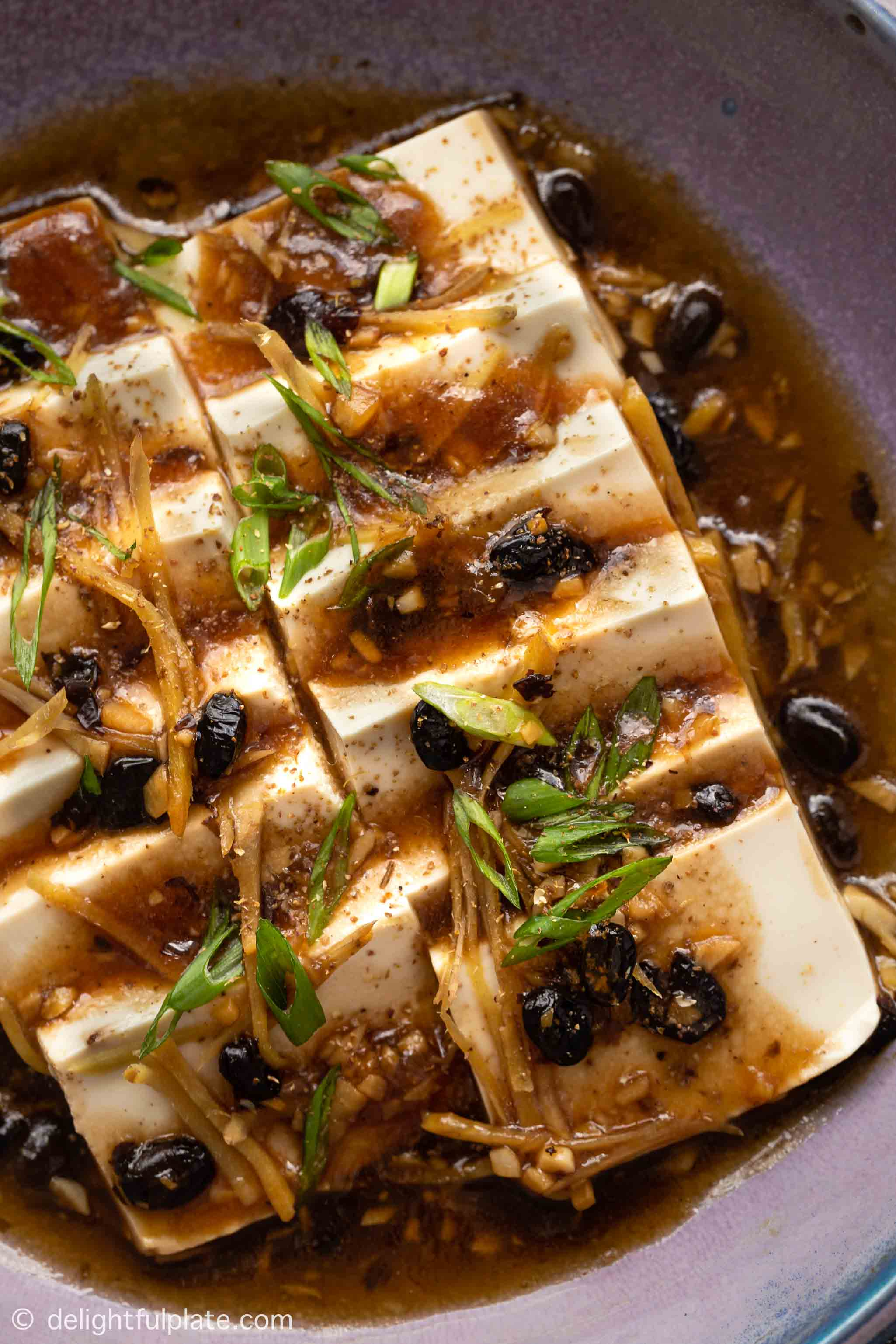 a plate of steamed silken tofu with black bean sauce