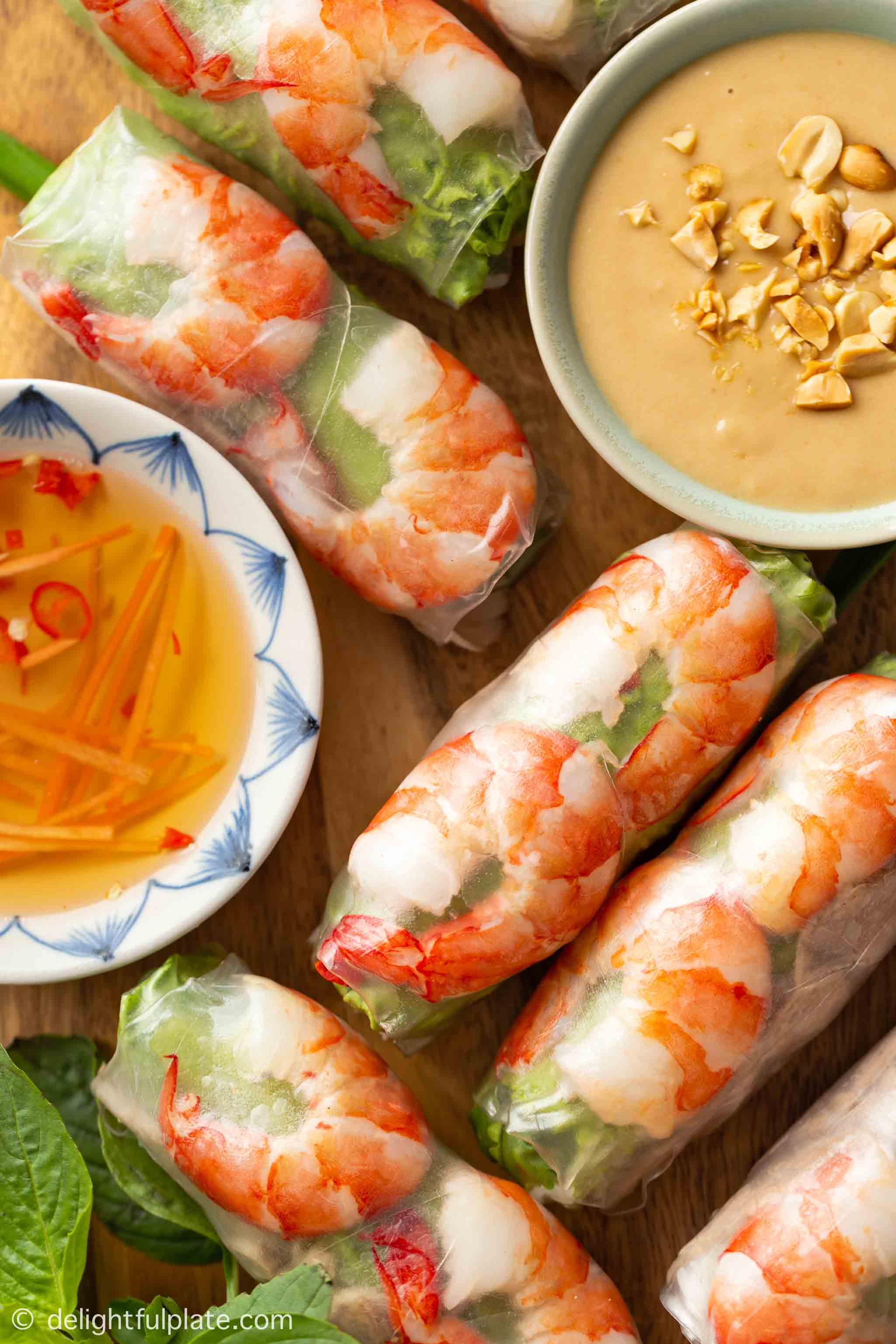 a serving plate with Vietnamese summer rolls and two types of dipping sauce