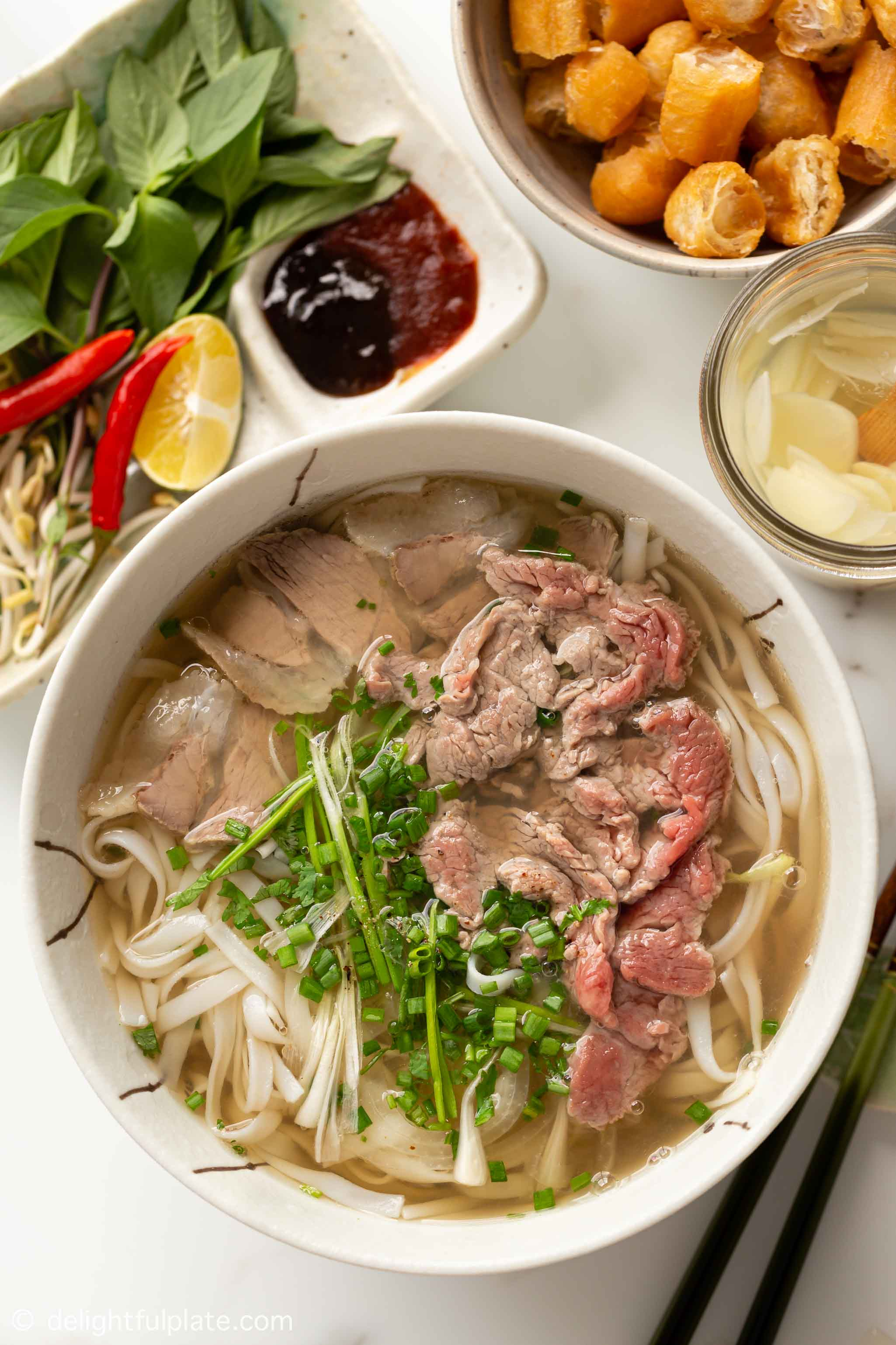 a bowl of Vietnamese pho noodle soup with well done beef and rare beef toppings.