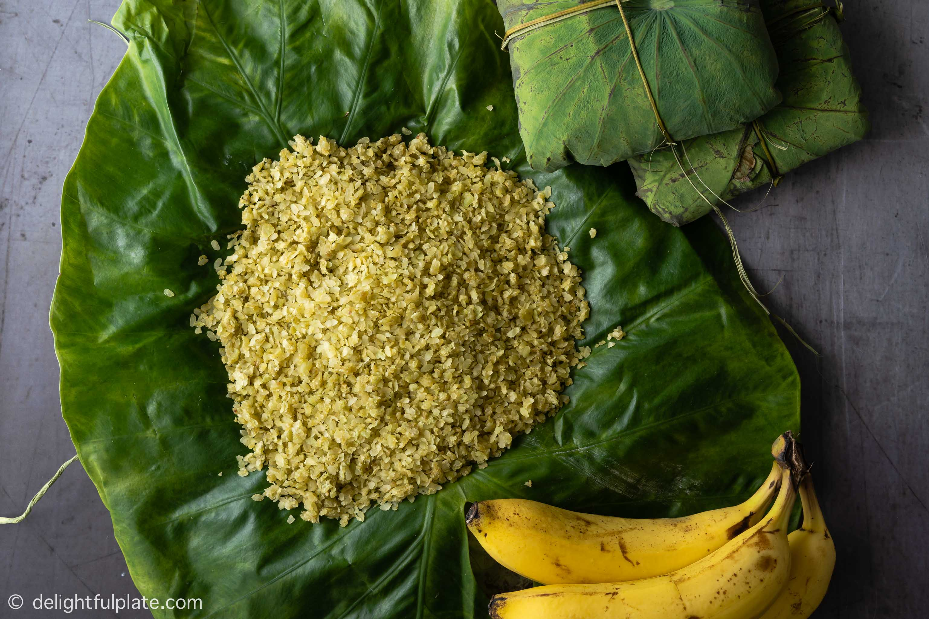 a small pile of Vietnamese green young rice, served with ripe bananas