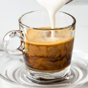 pouring milk into ginger coffee