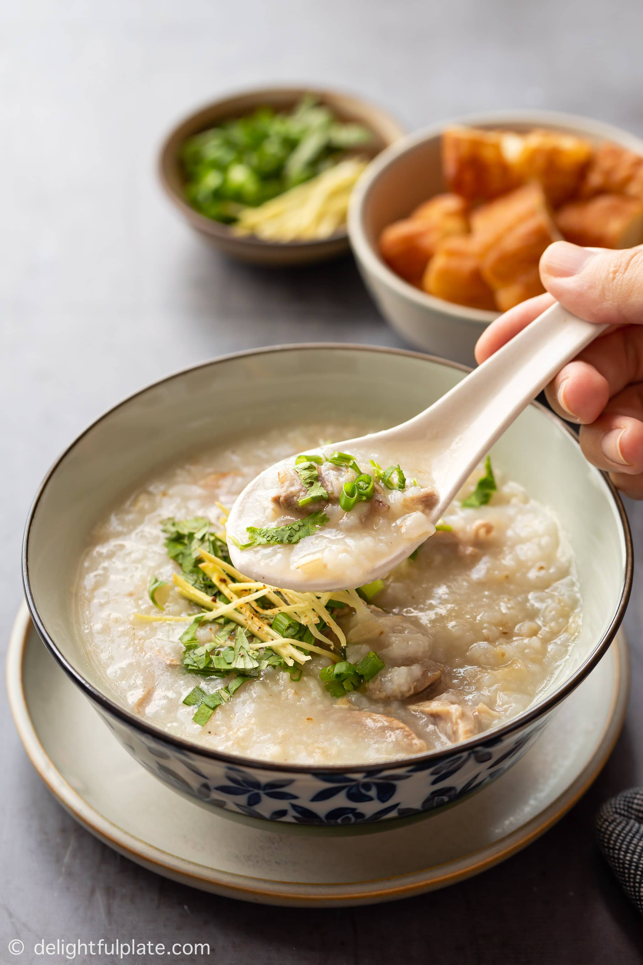 a bowl of duck congee, served with fried dough sticks (youtiao)