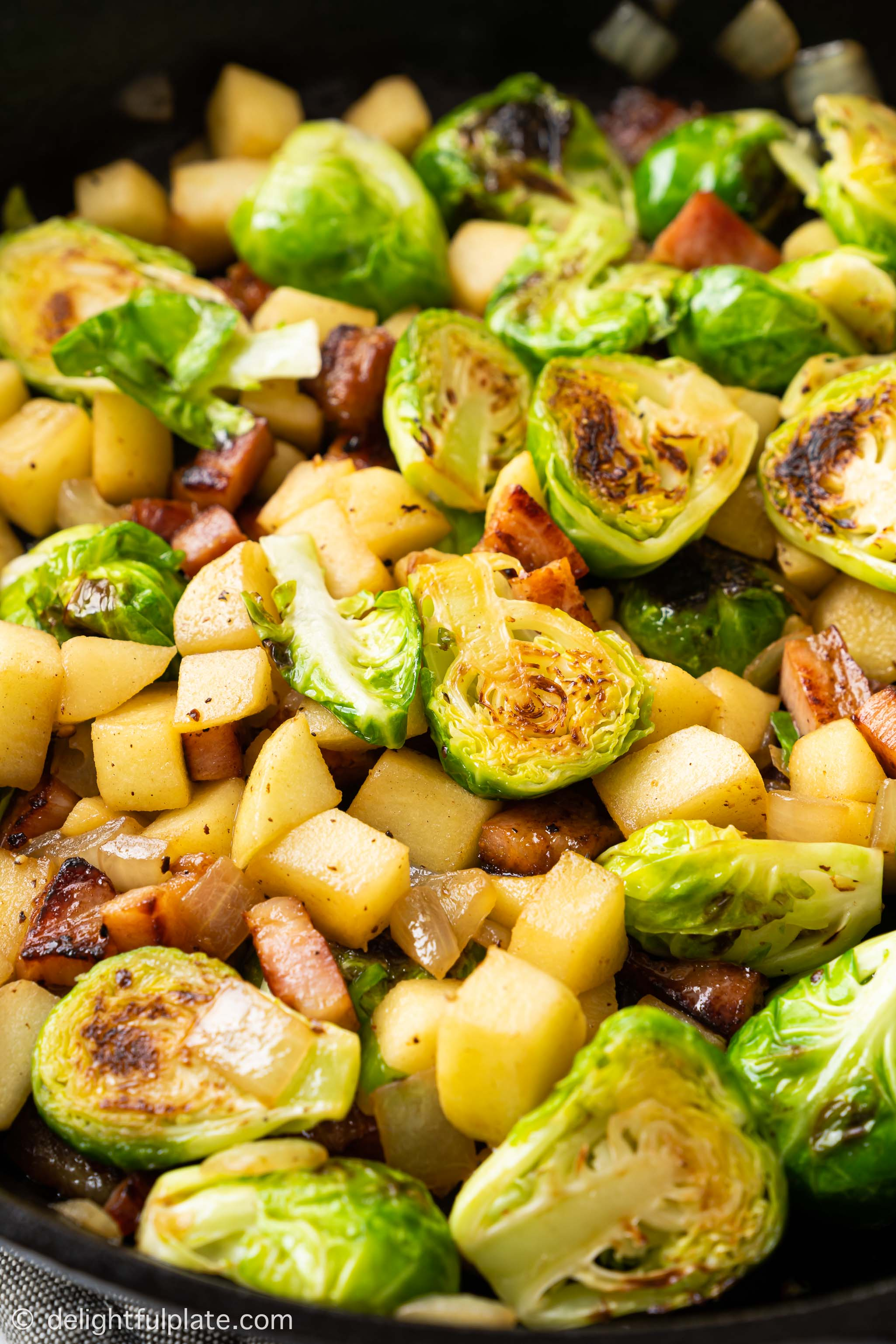 Sautéed Brussels Sprouts with Bacon and Apple in a cast iron pan