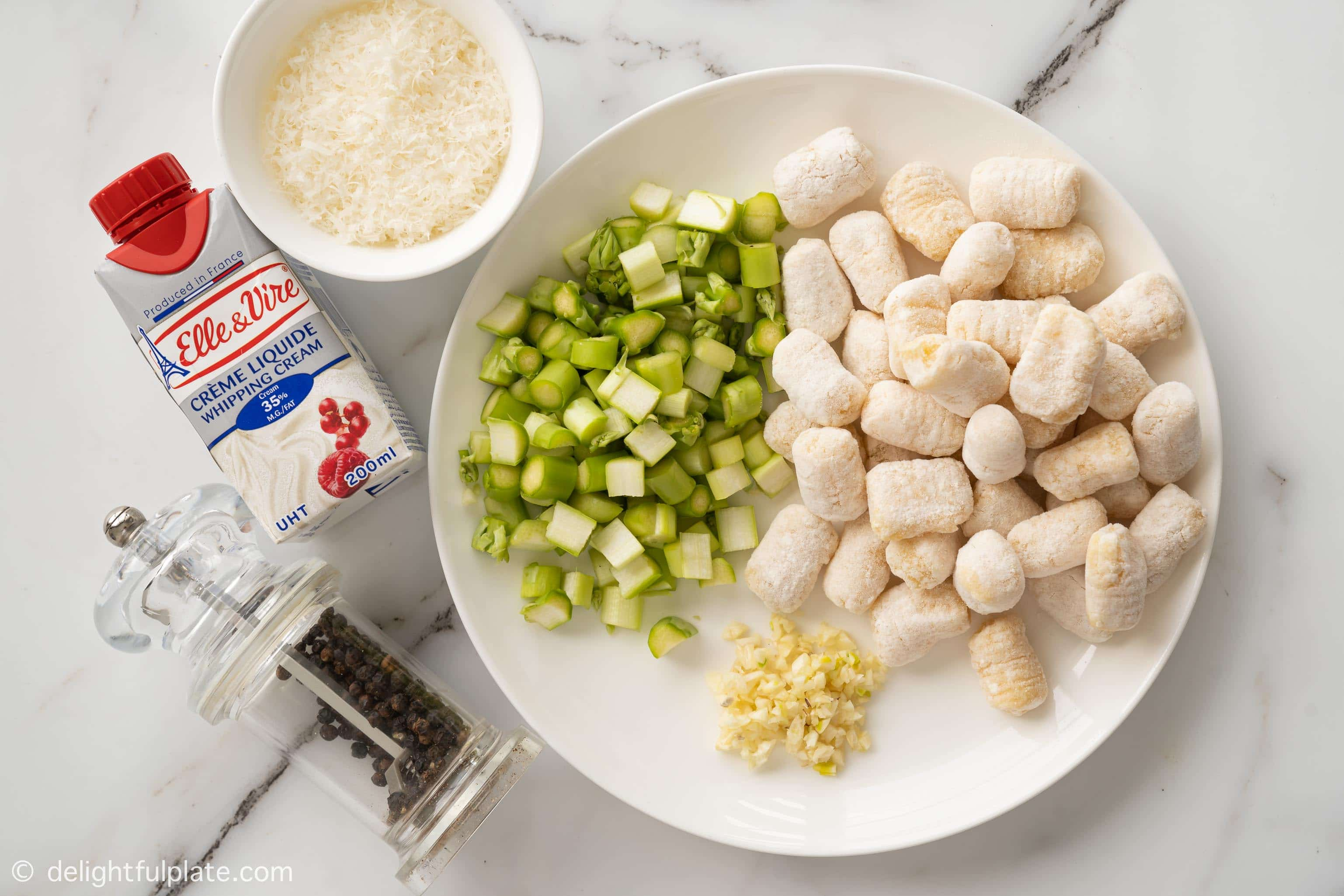 plates and bowls containing ingredients to make the dish: asparagus, gnocchi, garlic, parmesan, cream and black pepper