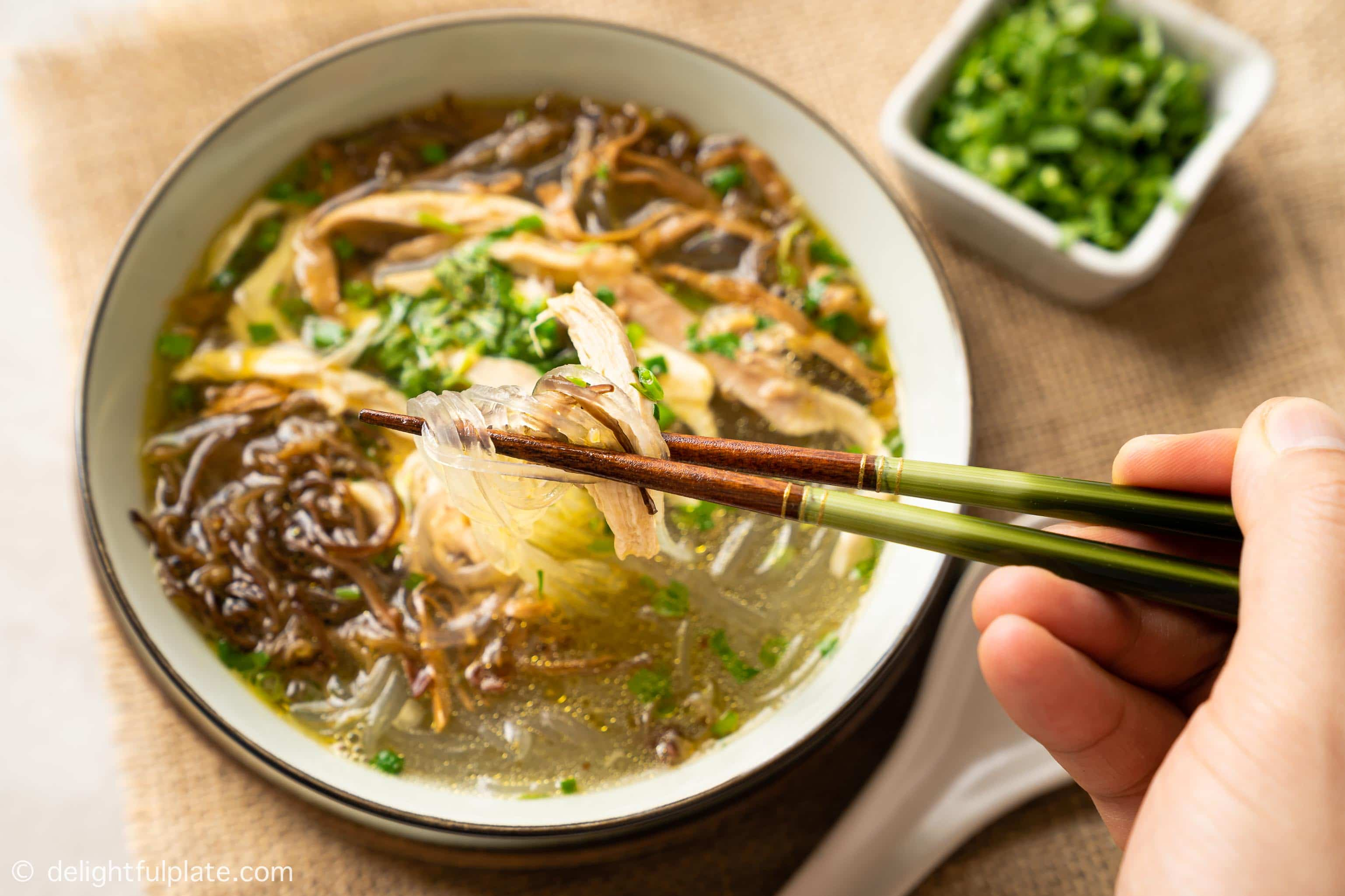 picking up chicken glass noodle soup from a bowl with chopsticks